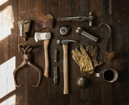 Picture of several old school tools on a dark hardwood floor